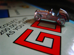 Image of metal car token on game board op top of the printed word GO