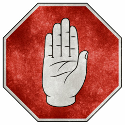Octagonal stop sign with picture of raised hand