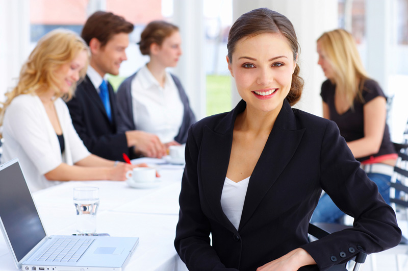 Image of multiple people in an office with focus on young woman smiling in front